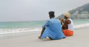 Vista traseira do suco de abacaxi bebendo dos pares afro-americanos na praia 4k filme