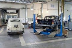 Vista traseira dois no pobeda clássico do gaz m20 dos carros do vintage do russo e chaika 13 em uma oficina de reparações nas boa fotos de stock royalty free