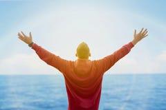 Vista traseira dos braços de espalhamento e de olhar do homem o oceano Imagem de Stock Royalty Free