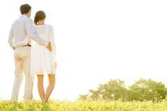Vista traseira dos braços eretos dos pares loving ao redor contra o céu claro imagem de stock