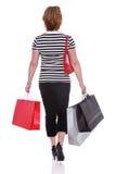 Vista traseira dos sacos de compras levando de uma mulher isolados. fotos de stock