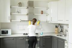 Vista traseira em um armário de lavagem da cozinha da jovem mulher imagens de stock royalty free
