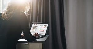 Vista traseira A mulher de negócios nova está sentando-se na tabela, trabalhando no portátil com gráficos, cartas, diagramas, pro imagens de stock