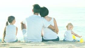 Vista traseira na família de quatro pessoas que senta-se na praia Fotografia de Stock