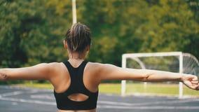 A vista traseira no atleta novo Woman no equipamento do esporte contratou na aptidão no campo de esportes no parque vídeos de arquivo