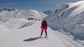 Vista traseira no movimento o esquiador que esquia abaixo da inclinação do esqui no recurso de montanhas vídeos de arquivo