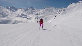 Vista traseira no movimento o esquiador que esquia abaixo da inclinação do esqui no recurso de montanhas filme