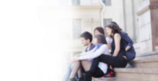 Vista traseira o grupo de amigos dos estudantes com um portátil no borrão imagem de stock royalty free