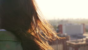 Back view. Wind blows long dark hair beautiful young women. girl standing on the roof at sunset. Slow mo Stock Footage