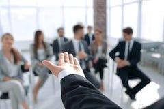 Vista traseira Treinador do negócio que gesticula sua mão na frente de um grupo de pessoas imagens de stock