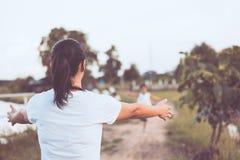 Vista trasera de la mano del aumento de la madre para esperar a su muchacha del niño fotografía de archivo libre de regalías