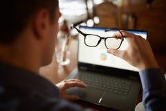 Vista trasera de la mano del hombre que sostiene las lentes delante de la pantalla del ordenador portátil con las cartas y los di foto de archivo libre de regalías