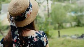 Vista trasera de la morenita bonita en sombrero del verano en fondo del campo almacen de metraje de vídeo