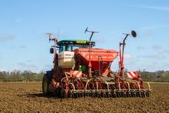 Vista trasera de la semilla moderna de la perforación del tractor de John Deere en campo Imagen de archivo