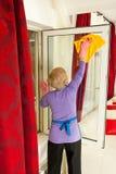 Vista trasera de la ventana de la limpieza de la mujer Foto de archivo libre de regalías