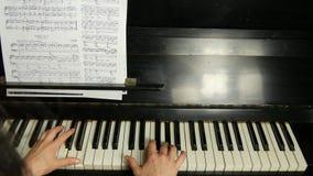 Vista trasera de las manos femeninas que juegan un pedazo apacible de música clásica en un piano de cola hermoso Mujer que juega  metrajes