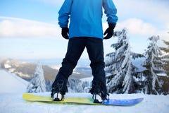 Vista trasera de las piernas del snowboarder en su tablero antes de la sesión backcountry del freeride en los pies del hombre del imagen de archivo