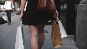 Vista trasera de los panieres que llevan del blogger femenino joven de la moda en ambas manos que caminan a lo largo de la cámara almacen de video