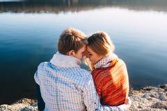 Vista trasera de los pares jovenes que abrazan cerca del lago Imagenes de archivo