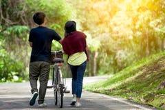 Vista trasera de los pares jovenes que caminan así como la bicicleta foto de archivo libre de regalías