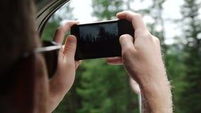 Vista trasera de los pares jovenes que conducen en coche y que toman las fotos del camino con smartphone metrajes