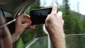 Vista trasera de los pares jovenes que conducen en coche y que toman las fotos del camino con smartphone almacen de metraje de vídeo