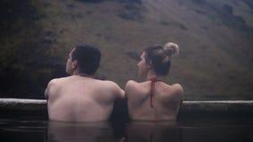 Vista trasera de los pares jovenes que se lavan en aguas termales en Islandia Hombre y mujer que viajan que se relajan en valle d almacen de video