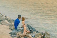 Vista trasera de los pares jovenes que se sientan junto en piedra delante del océano que disfruta de puesta del sol fotos de archivo libres de regalías