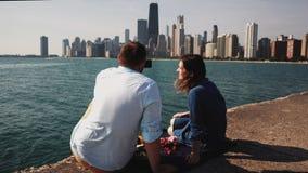 Vista trasera de los pares jovenes que tienen comida campestre en la orilla del lago michigan en Chicago, América El hombre toma  almacen de metraje de vídeo