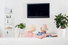 vista trasera de los pares mayores que miran la TV y el abarcamiento Imagen de archivo