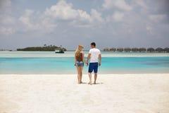 Vista trasera de los pares que llevan a cabo las manos y que caminan a la laguna azul del océano en Maldivas en el balneario de l fotografía de archivo libre de regalías