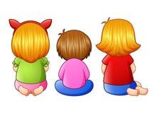 Vista trasera de poco muchacha tres que se sienta junto Imágenes de archivo libres de regalías