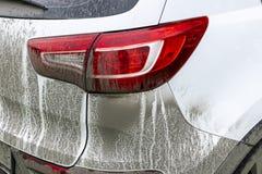 Vista trasera de un coche muy sucio Fragmento de SUV sucio Las linternas, la rueda y el tope sucios del coche campo a través con  Foto de archivo libre de regalías