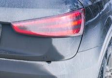 Vista trasera de un coche muy sucio Fragmento de SUV sucio Luces posteriores, rueda y tope sucios del coche campo a través con el Fotografía de archivo