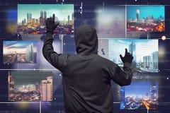 Vista trasera de un monitor virtual conmovedor del hombre del pirata informático Foto de archivo libre de regalías