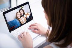 Vista trasera del blog video de observación de la mujer en el ordenador portátil en casa Imagenes de archivo