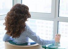 Vista trasera del café de consumición de la chica joven que mira en la distancia en ventana imagenes de archivo