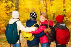 Vista trasera del cierre del soporte del grupo de los niños con las mochilas Imagen de archivo