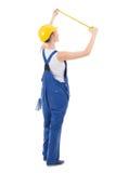 Vista trasera del constructor de la mujer en el workwear que mide algo con fotografía de archivo libre de regalías