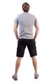 Vista trasera del hombre hermoso en camiseta y de los pantalones cortos que miran para arriba Fotografía de archivo