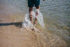 Vista trasera del pie desnudo del hombre que camina en la playa del verano La pierna ascendente cercana del hombre que camina en  imagenes de archivo