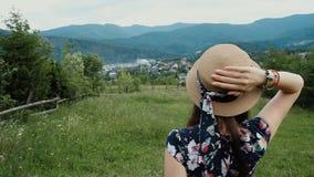 Vista trasera del sombrero del verano de la mujer que lleva y mirada en el Mountans durante sus vacaciones en el campo almacen de metraje de vídeo