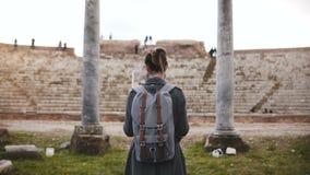 Vista trasera del turista femenino joven hermoso con la mochila y del mapa que exploran ruinas antiguas del anfiteatro en Ostia,  almacen de video