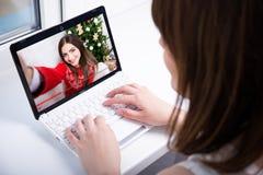Vista trasera del vídeo de observación del blog de la mujer en el ordenador portátil Foto de archivo libre de regalías
