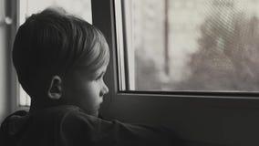 Vista triste e só da criança através da janela A criança é tiro preto e branco comprimido filme