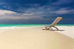 Vista tropicale della spiaggia di acqua stupefacente e della sedia vuota sulla sabbia per immagini stock libere da diritti