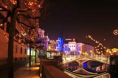 Vista a uno de tres puentes, con el río de Ljubljanica y los árboles adornados por la Navidad y Años Nuevos de día de fiesta Imagenes de archivo