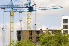 Vista urbana de las siluetas dos altos grúa industriales que trabajan en la construcción del nuevo edificio de ladrillo con los t imagen de archivo