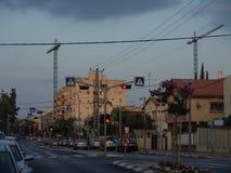 Vista urbana de un camino bilateral vacío con las muestras que caminan encendidas para arriba en naranja, coches parqueados y un  imagen de archivo libre de regalías
