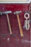 Vista vertical de dos martillos viejos con una manija de madera marrón y una abrazadera que cuelgan en la pared en un taller para imágenes de archivo libres de regalías